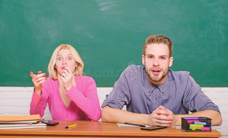 Grabben och flickan sitter p? skrivbordet i klassrum Undra om resultat Studera i h?gskola eller universitet Parv?nner arkivfoto