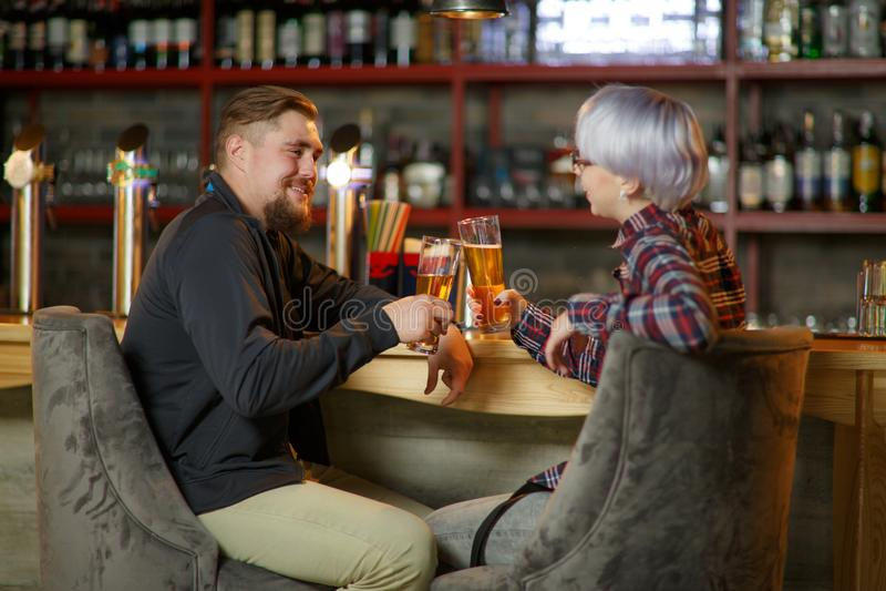 Grabben och flickan, spenderar fri tid i stång, meddelar och dricker öl inomhus fotografering för bildbyråer