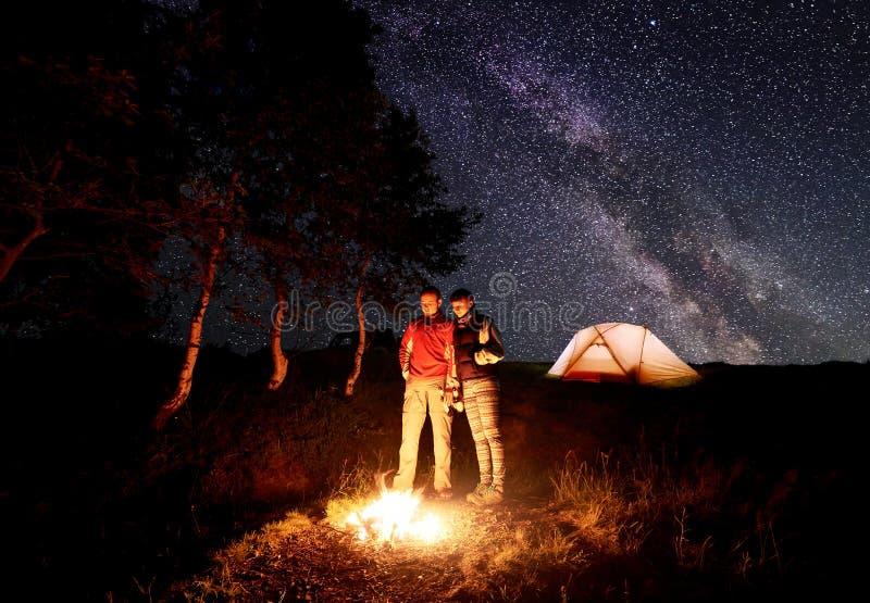 Grabben och flickan står vid brand med öl i deras händer under himlen som beströs med ljusa stjärnor och den mjölkaktiga vägen royaltyfria bilder