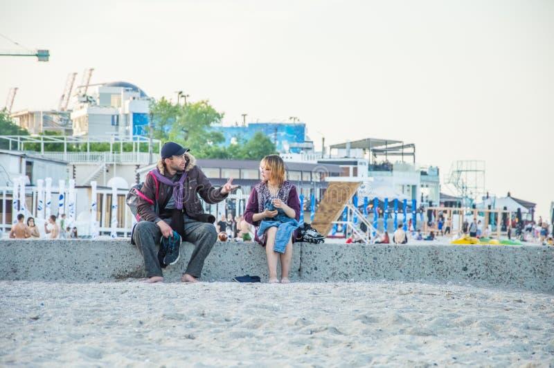 Grabben och flickan talar på stranden arkivbild