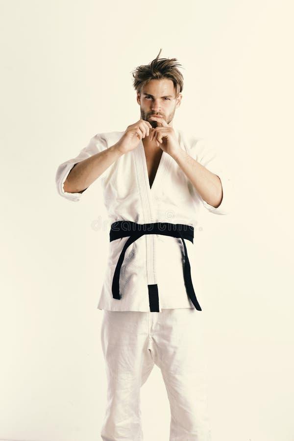 Grabben poserar i den vita kimonot med det svarta bältet Japansk karate arkivbild