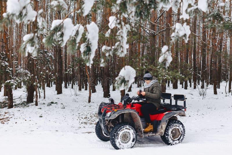 Grabben rider en motorcykel i ett snöig väder arkivfoto