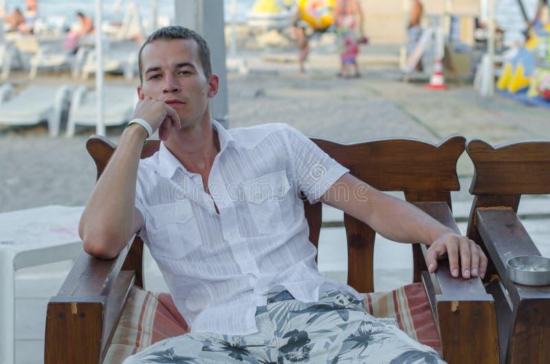 Grabben sitter nära stranden i kläder Den unga trötta mannen vilar sammanträde på en bänk vid havet efter en genomkörare arkivbilder
