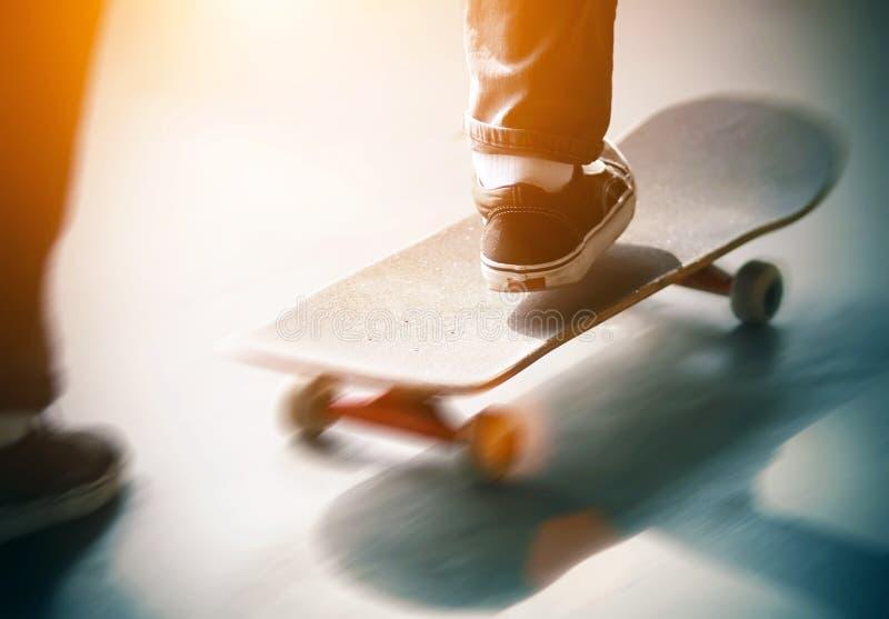 Grabben skjuter snabbt hans fot av asfalten och ritterna en skateboard arkivfoto
