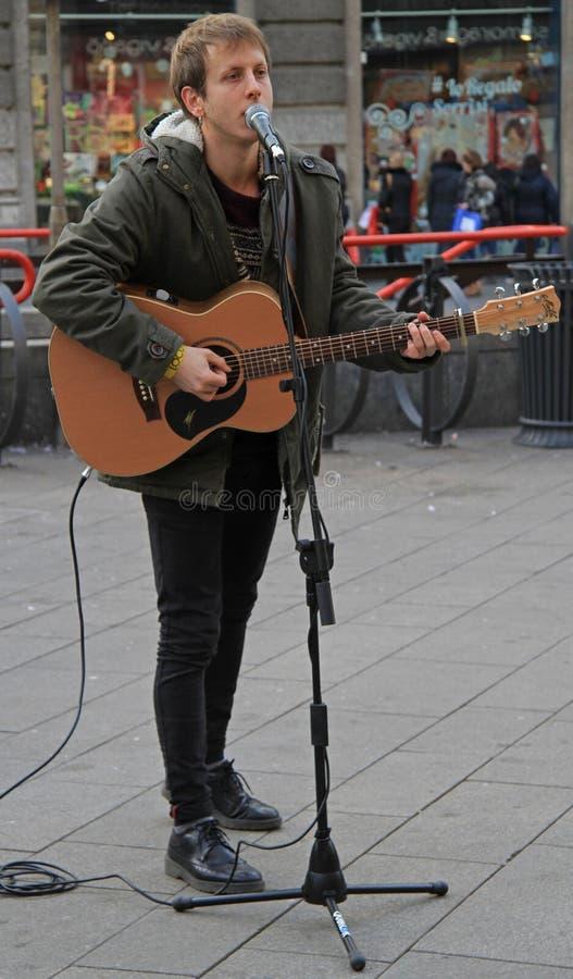 Grabben spelar den akustiska gitarren utanför i Milan fotografering för bildbyråer