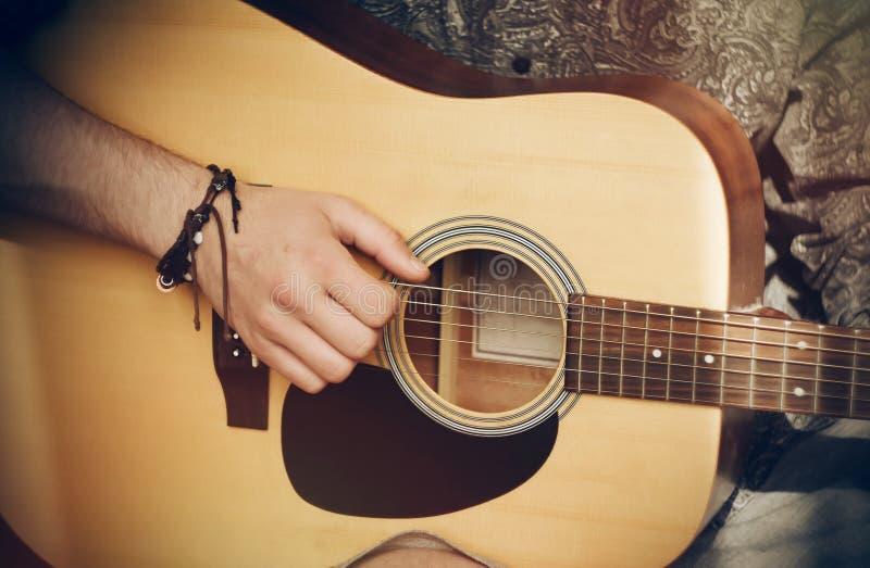 Grabben spelar en akustisk gitarr i stilen av 80-tal royaltyfri foto
