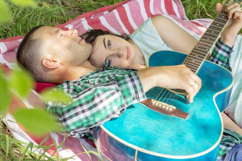 Grabben spelar gitarren till flickvännen Romantiskt m?te sommarpicknickpar som lägger på gräset royaltyfria bilder