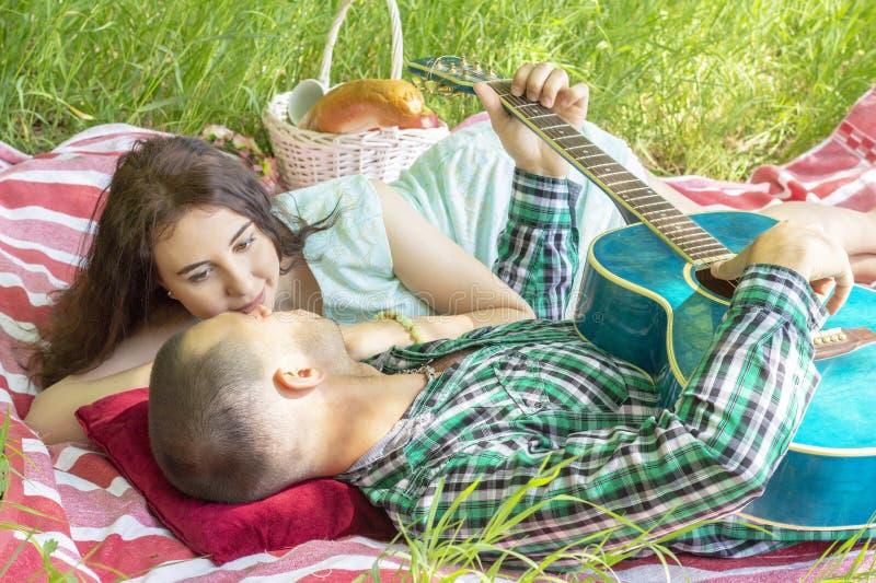 Grabben spelar gitarren till flickvännen Romantiskt m?te sommarpicknickpar som lägger på gräset royaltyfri fotografi