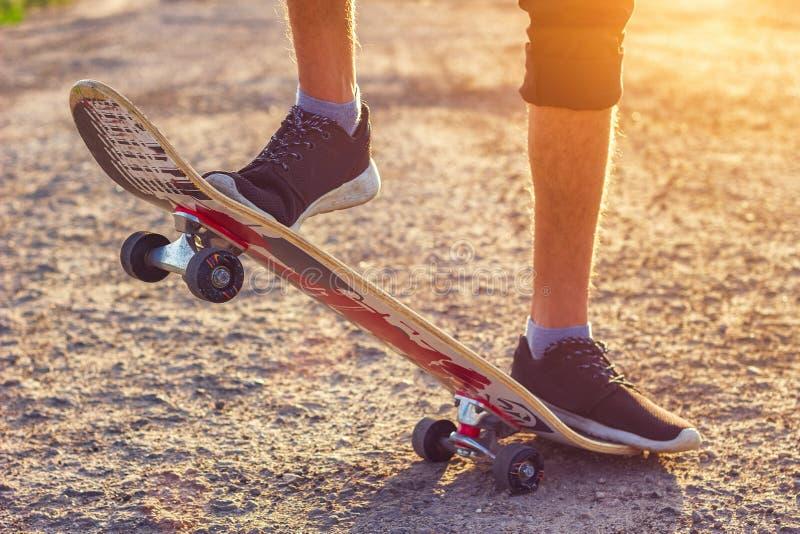 Grabben står på en skateboard är på den härliga toningen för vägen arkivbild