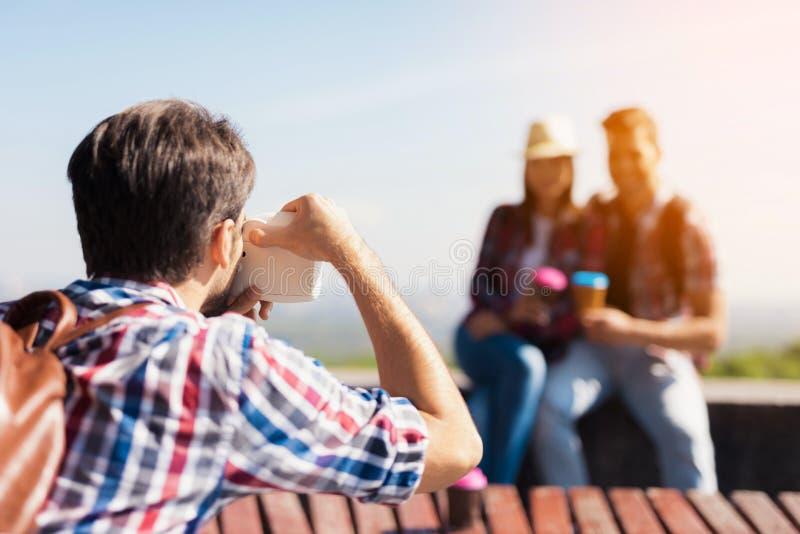 Grabben tar bilder av en grupp av turister som sitter i parkera på bänken royaltyfri foto