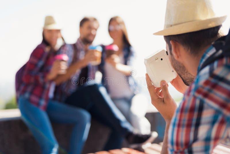 Grabben tar bilder av en grupp av turister som sitter i parkera på bänken fotografering för bildbyråer