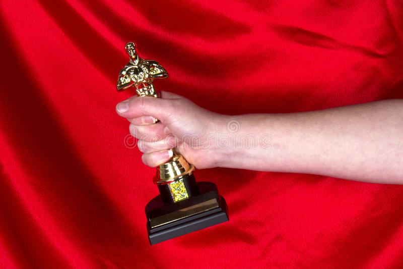 Grabbing an Oscar. Arm showing with a hand grabbing onto an Academy Award Oscar statuette stock images