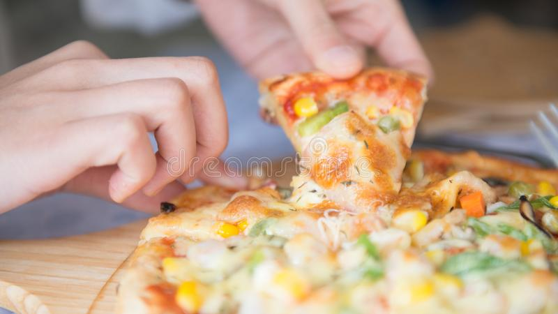 Grabbing slice of pizza royalty free stock image