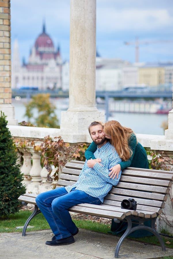 Grabbsammanträde på bänken, flickaanseende bak böjde till kyssen arkivbild