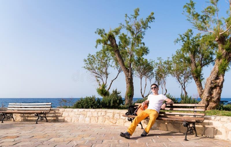 Grabbsammanträde på en bänk nära havet arkivbild