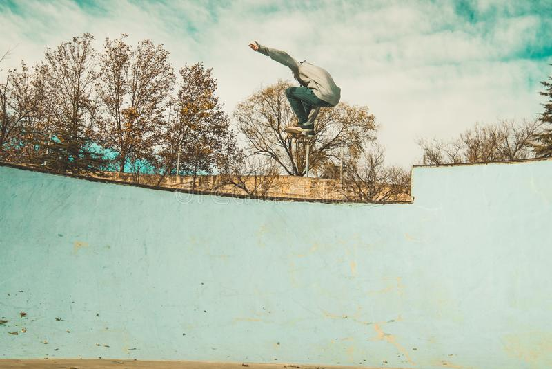 Grabbskateboarder som rider en skateboard på en skatepark Ung man som hoppar med en skateboard arkivbilder