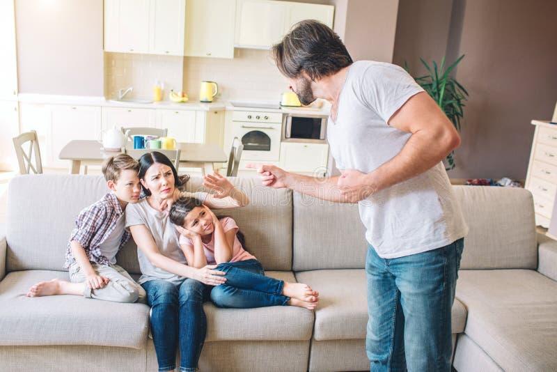Grabbställningar och blick på frun med ungar Han är tokig Manpunkter på dem Kvinnan och ungar göras ont De ser ledsna och olyckli royaltyfri bild