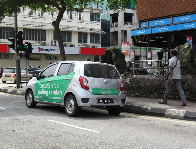 Grab Vehicle With Promotional Ads Painted Around Its Side. The ride-hailing/ride-sharing service GrabCar in the streets of Ipoh city, Malaysia stock photos