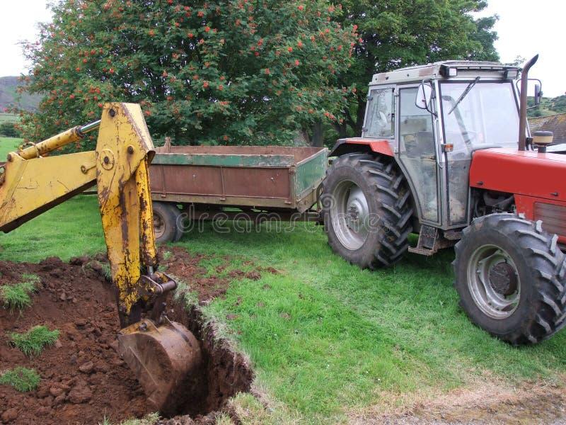 Grabende Grundlagen des gelben Gr?bers f?r eine L?schung zu einem Bungalow mit Traktor und Anh?nger stockbilder