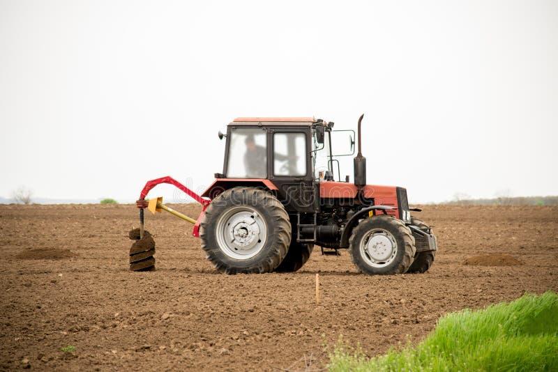 Grabende Löcher des Traktors für das Baumpflanzen lizenzfreies stockfoto