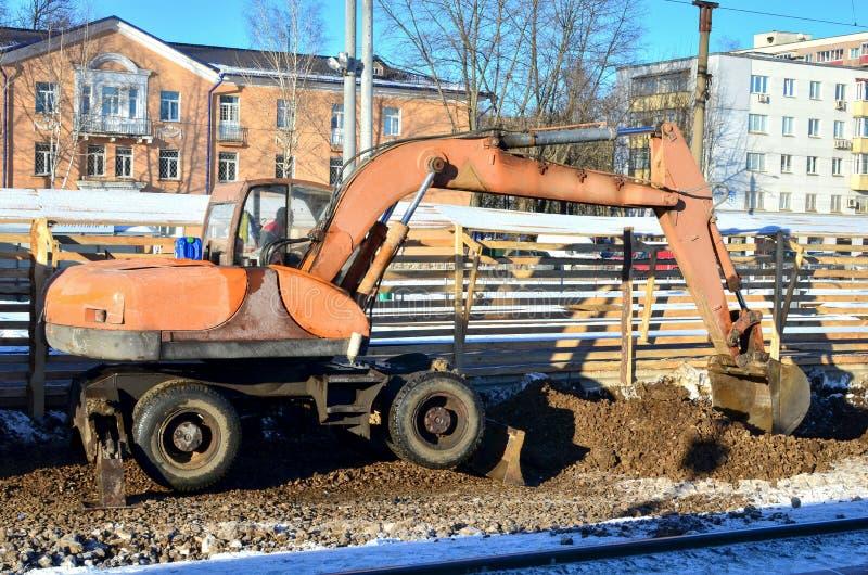 Grabende Maschine des Baggers gräbt Erde mit Steinen mit einem Eisenschöpflöffel lizenzfreie stockfotografie