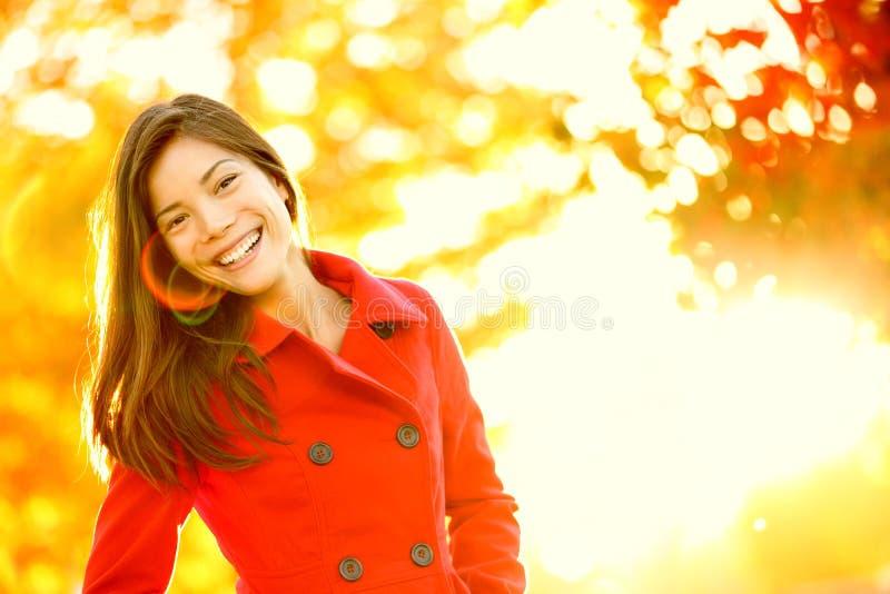 Grabenmantelfrau des Herbstes rote im Sonneaufflackernlaub stockbilder