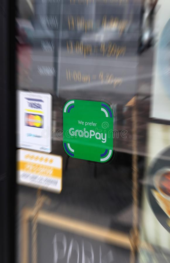 GrabPay Sticker With Zoomed In Blur. GrabPay sticker on a glass door at a cafe in Ipoh Oldtown Malaysia with zoom-in blur stock photos