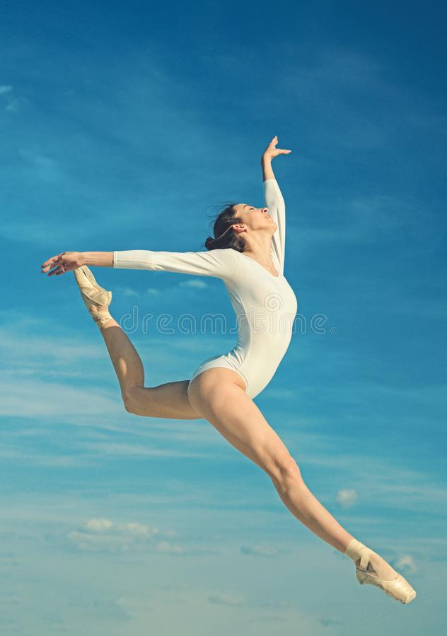 Grace and beauty. Classic dance style. Young ballerina jumping on blue sky. Cute ballet dancer. Pretty woman in dance stock image