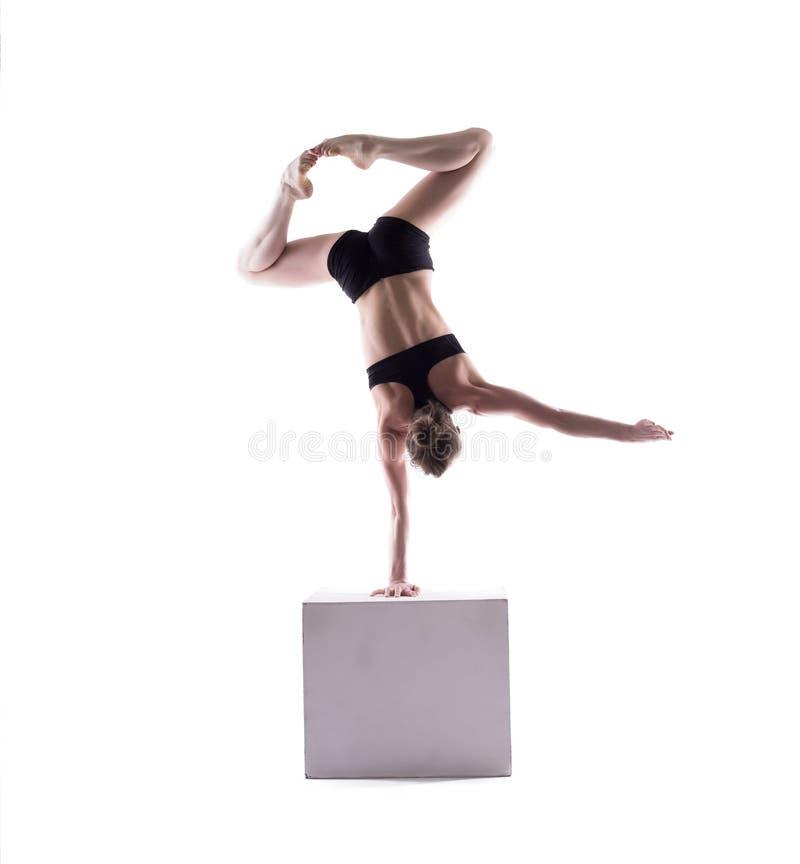 Graceful acrobat posing on cube