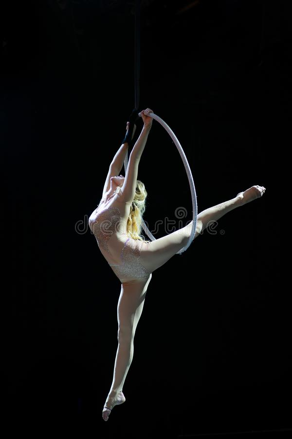 Graceful aerial acrobat doing her performance with a hoop isolated on black royalty free stock photography