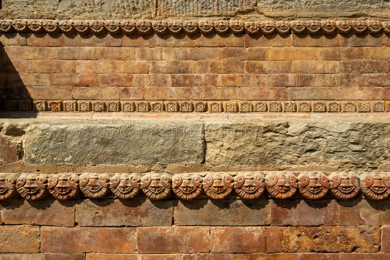 Graceful ancient stone carving. Brown stone texture. Wall of an old Hindu temple at Durbar Square in Kathmandu, Nepal.  royalty free stock photography