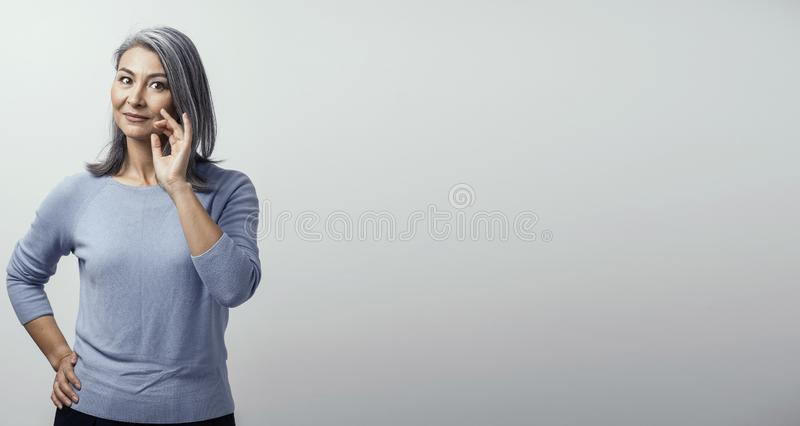 Smiling Asian woman touches her grey hair stock photo