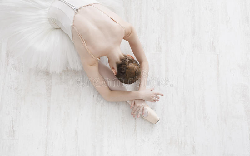 Graceful Ballerina stretching, ballet background, top view. Beautiful graceful young ballerina in pointe shoes at white wooden floor background, top view from stock image