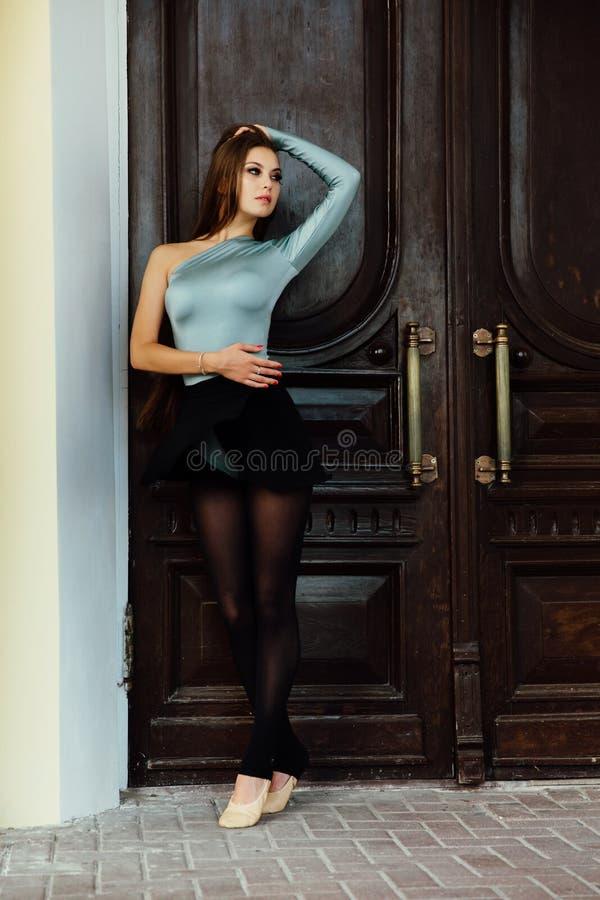 Graceful beautiful girl ballerina posing on the street of the vintage theater wood door. royalty free stock photos