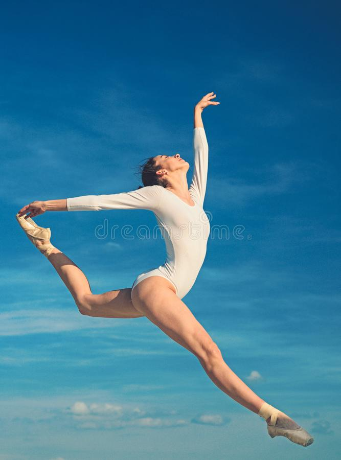 Graceful beauty. Concert performance dance. Young ballerina jumping on blue sky. Classic dance style. Cute ballet dancer stock photography