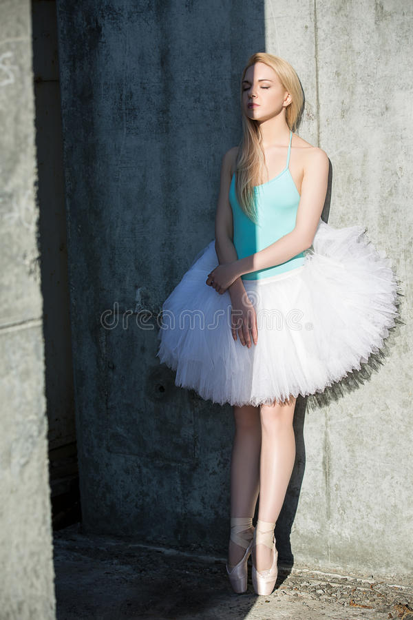 Graceful dancer with blond hair on the background. Of gray concrete wall texture. Light and shadow divides the body in half. Shooting outside the studio in an stock photos