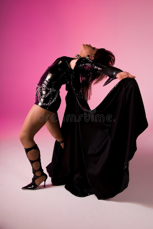 Graceful Drag queen. Drag queen wearing a latex outfit, holding the edges of the cape and arching back. Pink background stock photography