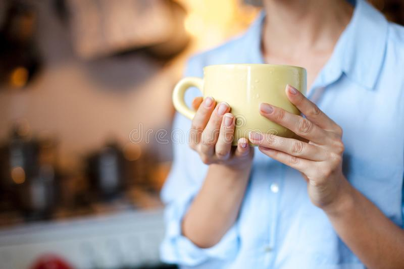 Graceful female hands hold cup of coffee. Young woman is drinking tea in cozy home kitchen. royalty free stock image