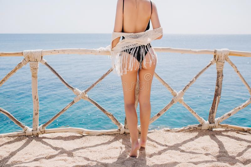Graceful girl in black bikini and knitted pareo resting outside and posing on sea background in warm sunny morning stock photos
