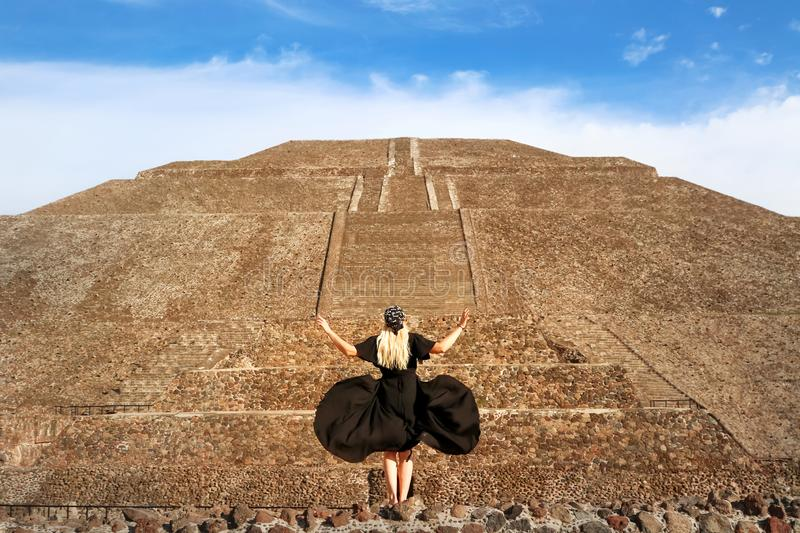 Graceful girl in a black dress and bandana with skulls on the background pyramid of the Sun in Teotihuacan. The great ancient sights of Mexico stock images