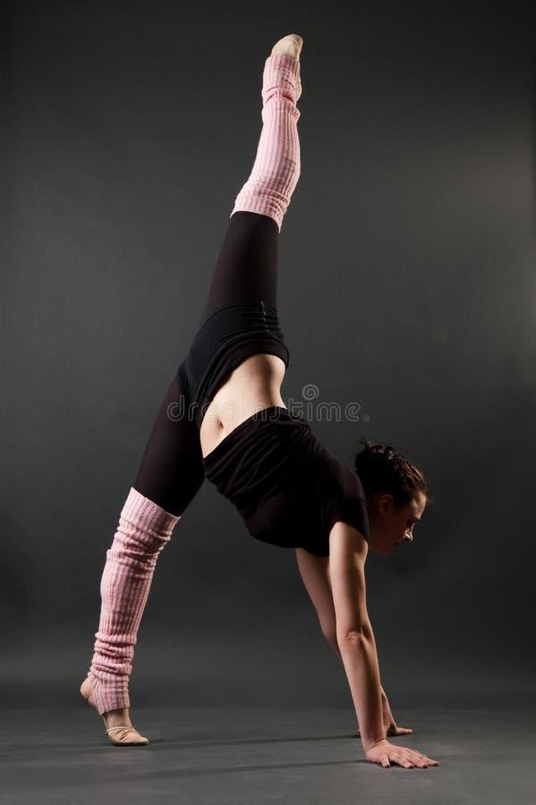 Graceful gymnast. Standing in splits against dark background royalty free stock image