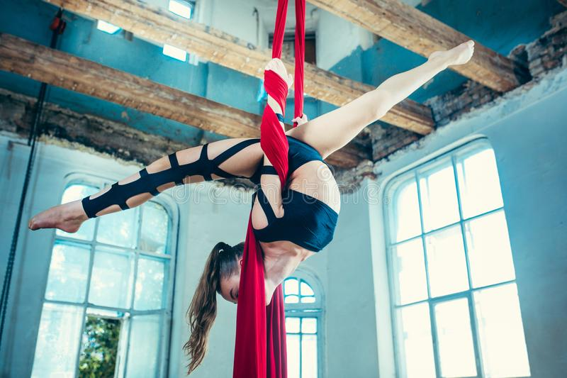 Graceful gymnast performing aerial exercise at loft royalty free stock photo