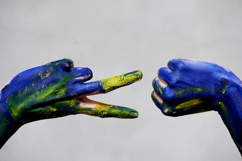 Graceful hands of the artist . Hands in blue and yellow paint. Creator, creativity.Yoga for hands. A game of Rock paper royalty free stock image