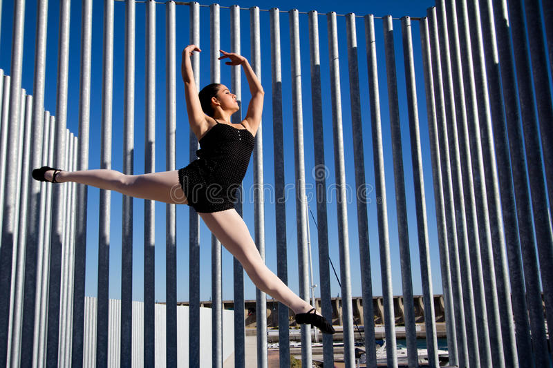 Graceful jumping of a classic dancer in Malaga. She wears dark clothes, blackshoes and white tights. She raises her arms over her head. In the background there royalty free stock photos