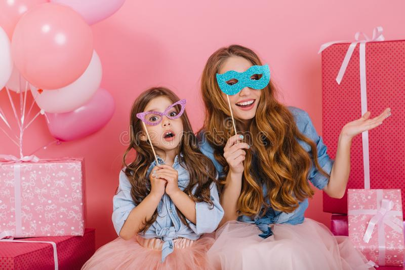 Graceful little girl with surprised face expression sitting next to her smiling curly mother surrounded pink present. Boxes. Pretty young women arranged a funny royalty free stock image