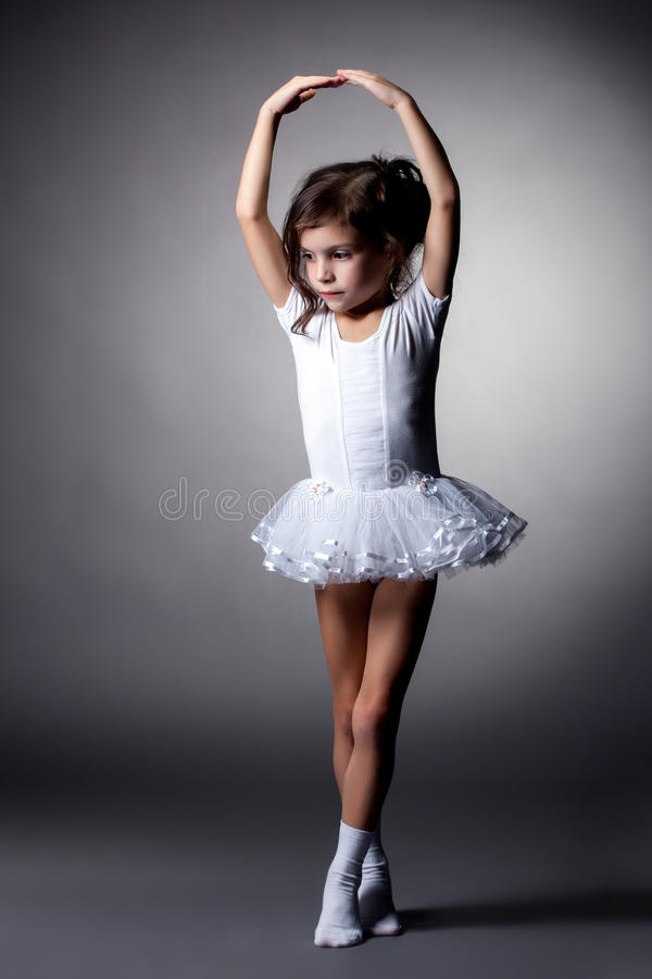 Graceful little gymnast performs in studio royalty free stock photography
