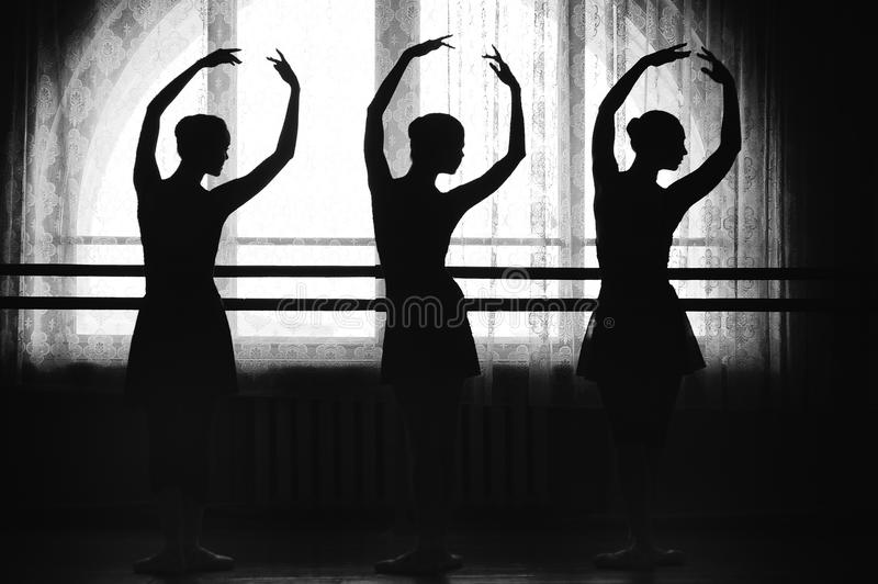 Graceful silhouettes of ballerinas on a window background royalty free stock photography