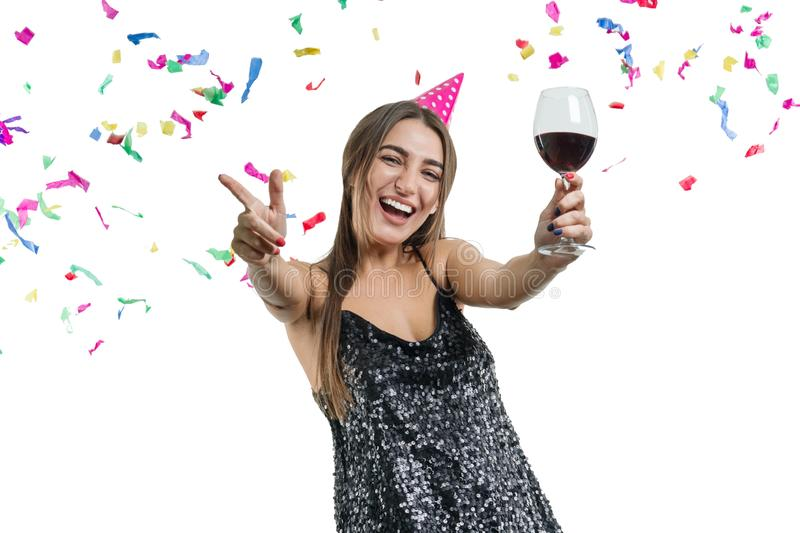 Graceful, smiling young brunette girl in party hat with glass of red wine dancing under confetti and laughing, white isolated royalty free stock image