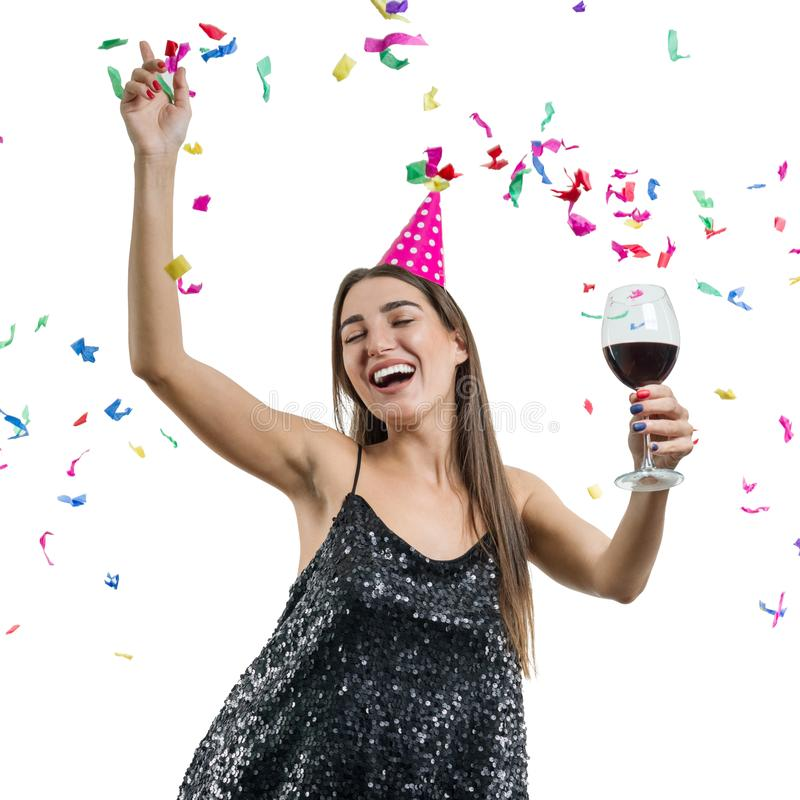 Graceful, smiling young brunette girl in party hat with glass of red wine dancing under confetti and laughing, white isolated stock photography