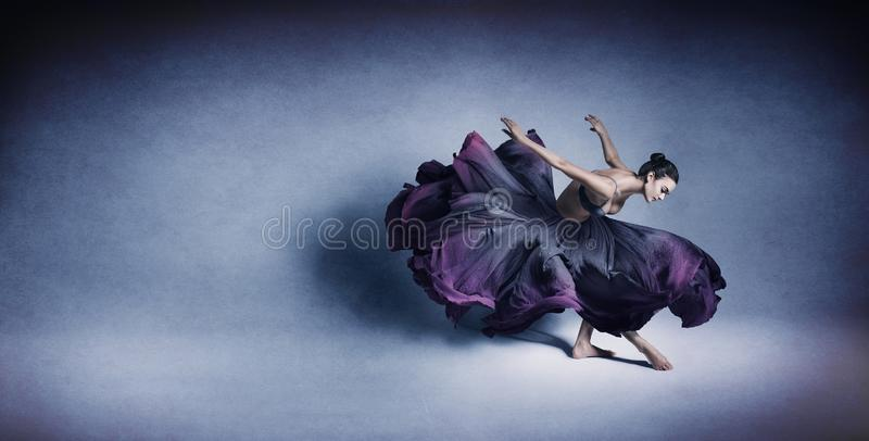 Graceful woman dancing in flowing dark blue dress royalty free stock photo